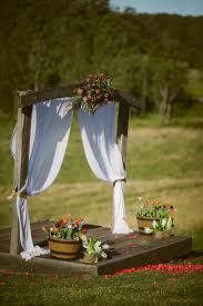 The Rustic Timber Archway Decorated With Bright Coloured Flowers And Beautiful White Flowing Chiffon