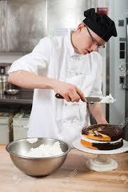 glacer en cuisine chef masculin glacer un gâteau dans la cuisine commerciale banque d
