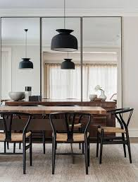 Modern Dining Space With Black Pendant Lights Midcentury Chairs And Floor To Ceiling Oversized Mirrors
