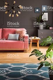 dunkle wohnzimmer interieur mit modernen le poster an wand frischpflanzen und pulver rosa sofa mit kissen in das realistische foto stockfoto und
