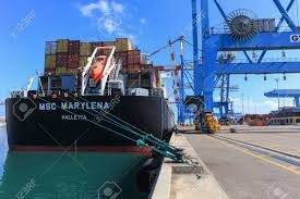 Port Dock With Container Ship And Various Brands Colors Of Shipping Containers Stacked In A