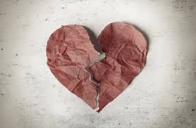 A Red Heart Crumpled Up On Paper Is Torn In Half