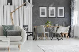 beige sofa mit kissen und designerle im esszimmer mit plakaten auf grauer wand über tabelle