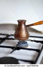 kaffee gebraut in einer kupferzezve auf einem gasofen in