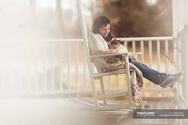 Girl Holding Cat In Rocking Chair — Color Image, Side View ...