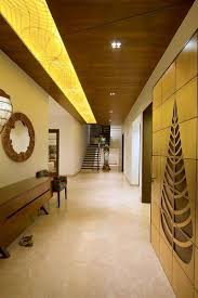 Stunning Golden Wall Art Concealed Dim Yellow Lighting And A Dark Wooden Ceiling Are All Complimented With Light Pastel Marble Flooring Giving Each