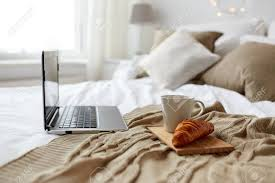 technologie urlaub weihnachten innen und winter konzept gemütliches schlafzimmer mit laptop computer kaffeetasse und croissant auf dem bett zu