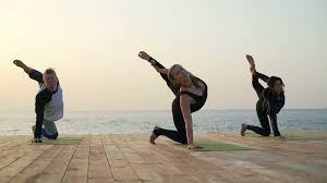Three Friends Does Yoga Exercise On The Wooden Pier Slow Motion Stock Video Footage