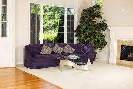 horizontale foto formalen wohnzimmer mit wildledercouch glastisch teppich große fenster pflanzen kamin und holzböden