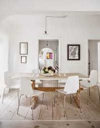 Bright And Airy Dining Space With Unfinished Wood Floor Panels Modern White Chairs Wooden Farm Table Light Fixtures Candlesticks
