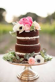 A beautiful unfrosted chocolate wedding cake topped with fresh flowers