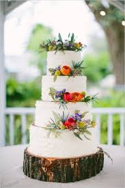 Beautiful White Wedding Cake With Floral Decor Displayed On A Wooden Slice