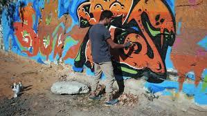 Graffiti Artist Painting On The Street Wall Handsome Man With Aerosol Spray Bottle Spraying