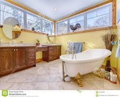 altmodisches gelbes badezimmer mit hölzernen kabinetten