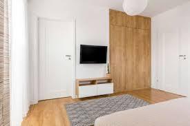 praktische und minimalistische schlafzimmer tv wand mit geräumigem holzkleiderschrank