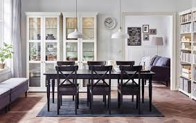 A Large Dining Room With Black Extendable Table Chairs And Glassdoor Cabinets In