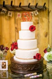 A Four Tier Wedding Cake Decorated With Red Roses Natural Ribbons And