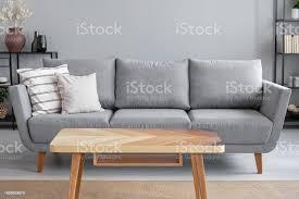 holztisch und große graue mit kissen im wohnzimmer trendige wohnung echtes foto mit textfreiraum an der wand stockfoto und mehr bilder