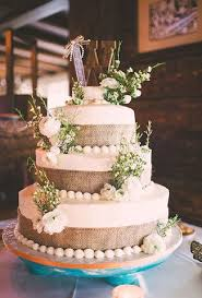 Three Tiered Wedding Cake With Burlap Wrapped Tiers Fresh White Ranunculus And Greenery