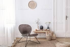 dunkle moderne korbstuhl in einem weißen wohnzimmer interieur mit einer holzbank und dekorationen aus naturmaterialien gefertigt stockfoto und mehr