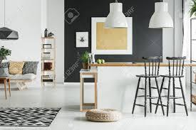 puff auf dem boden in der nähe küche mit barhockern und gemusterten kissen auf dem sofa im stilvollen wohnzimmer