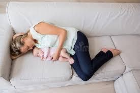 mutter die mit ihrem baby im wohnzimmer schläft stockbild