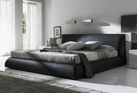 black leather bed frame with headboard and grey bed sheet on the