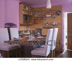 White Loosecovers On Chairs At Wood Table In Modern Mauve Kitchen Dining Room With Utensils And Shelves Wall1010