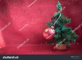 A Small Christmas Tree On Gold Stand Is Decorated With One Big Red Ball