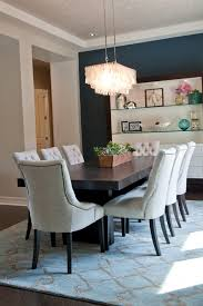 Eight Off White Tufted Chairs Surround A Dark Wood Table In This Chic Transitional Dining Room Blue Accent Wall Attracts The Eye To Built