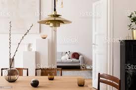 stilvolles scandi interieur des wohnraums mit designholztisch stühlen sofa und goldpendelleuchte wohnzimmer mit designaccessoires und klavier schöner