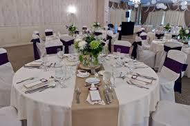 Rustic Burlap Wedding Decorations With Small Flowers In Glass Jar On Round Tables Also White Covered Chairs