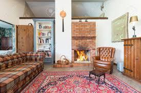 rustikales gemütliches wohnzimmer mit gemauerten kamin sofa sessel und altmodischen teppich
