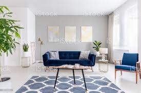 echtes foto einem eleganten wohnzimmer interieur mit blauem sofa sessel couchtisch gemusterten teppich und gemälde an der grauen wand stockfoto