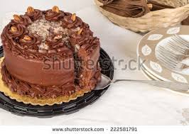 slice on cake knife cut from beautiful German Chocolate Cake surrounded by dessert dishes