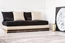 kissen auf schwarzen sofa in weiß wohnzimmer interieur mit mond poster und teppich echtes foto stockfoto und mehr bilder beschaulichkeit