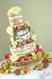 Naked Wedding Cake With Fresh Fruit And White Roses On A Rustic Tree Log Stand