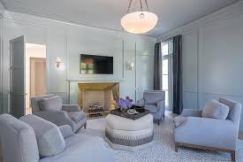 light gray paneled sitting room with brass fireplace surround
