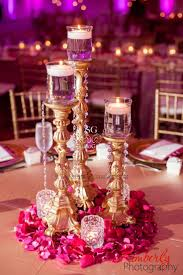 Simple Candlestick Centerpiece With Surrounding Flowers And Votives Great Indian Wedding Reception Idea Its More Cost Effective Than Using