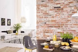 geräumiges modernes wohnzimmer mit esstisch aus holz mit frühstück