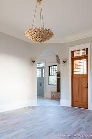 living room light gray walls grey gold chandelier black window