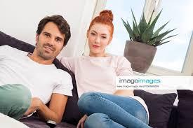stockfoto junges liebespaar sitzt im wohnzimmer auf cou