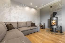 geräumiges graues wohnzimmer mit großem sofa kamin und venezianischem stuck