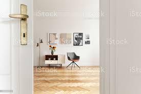 weiße wohnzimmer interieur mit fischgrätmuster stock gold le galerie auf wand und grau stuhl stehend neben schrank mit sonnenblumen in echtes foto