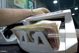 bureau de change 11 a counts 100 bolivar bills on a machine at a bureau de change in