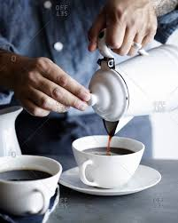 Man Pouring Coffee Into Cup From Metal Pot Stock Photo