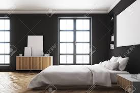 seitenansicht eines modernen luxusschlafzimmers mit schwarzen wänden ein großes bett in der mitte des raumes zwei bücherregale an seinen seiten ein