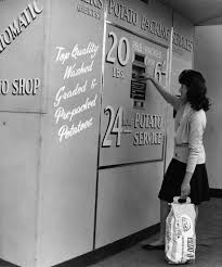 A Woman Operating The First Vending Machine In Britain To Sell Potatoes At Greengrocers Shop