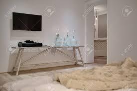modernes interieur mit weißen wänden und parkett es gibt einen holztisch mit kerzen in flaschen soundbar schal tv bett mit einem plaid eingang