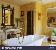 antiker spiegel über dem waschbecken im gelben badezimmer
